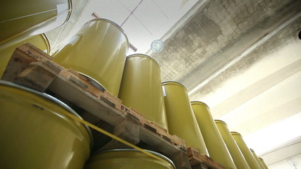 New yellow barrels inside a storage warehouse slider shot