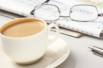 a cup of coffee, glasses and a pen on papers