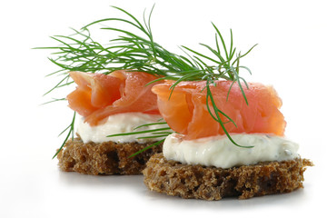 two  salmon canapes with fresh dill garnish, isolated on white b