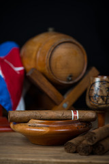 cigars with rum barrel on table