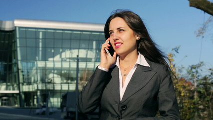 Businesswoman talking on cellphone and smiling, steadycam shot