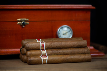 Cuban cigars on table with handmade humidor in background