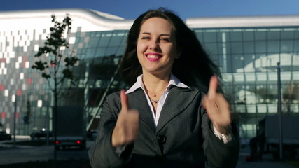 Happy businesswoman showing thumbs up to the camera