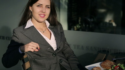 Businesswoman smiling to the camera outside the cafe