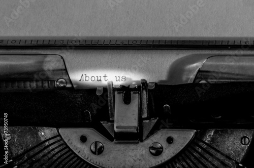 """Poster Typewriter with the """"About us"""" text typed on a white paper."""