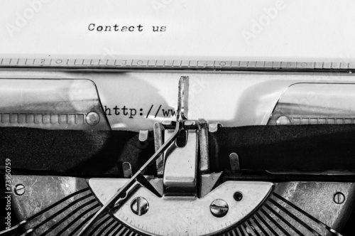 """Poster Typewriter with the """"Contact us"""" text typed on a white paper."""