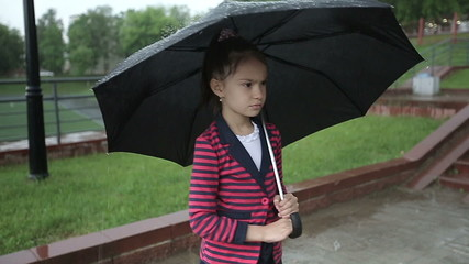 Lonely child girl in the rain under an umbrella slow motion.