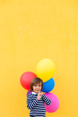 kid with color balloons on a yellow wall