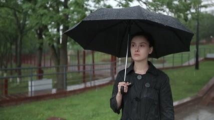 Lonely sad woman in heavy rain under an umbrella slow motion
