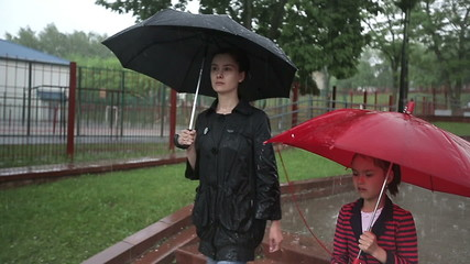 Mother and daughter walking on the street in heavy rain