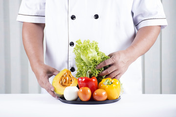 cook holds tray of vegetable