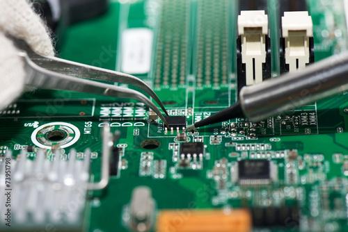 Leinwanddruck Bild Electronic component held with tweezers on motherboard