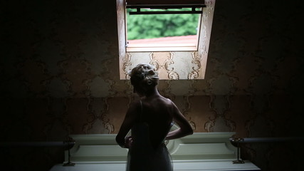 Elegant bride wears a wedding dress standing at the window