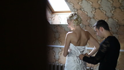 Bride dresses before a mirror, it helps her fiance