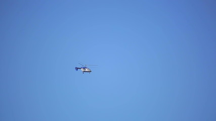 Small helicopter flies on blue sky background