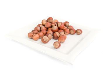 Hazelnut on a white plate and on a white background