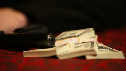 Pistol and three packs of dollars on the table with a red cloth