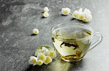 cup of japanese green tea with jasmine flowers and lemon
