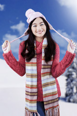Cheerful girl with jumper near mountain