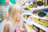 Adorable girl sit with set of good in shopping cart in supermark