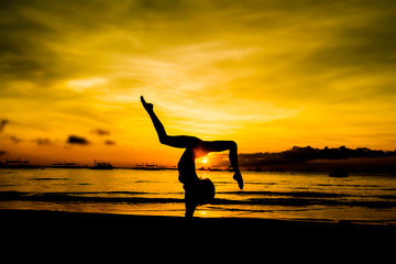 silhouette of jumping girl on tropical sunset sea and sky backgr