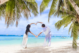 young loving couple making heart on tropical sea and beach backg