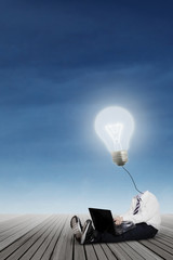 Little boy with lamp head using laptop