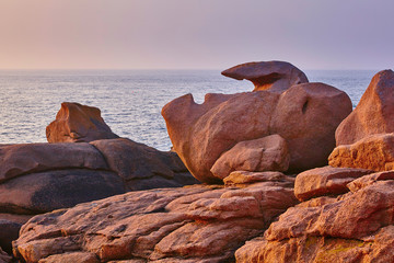 Scenic view of pink granite coast at sunset