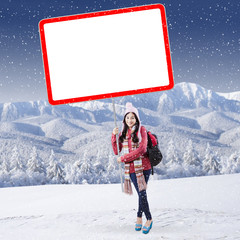 Schoolgirl with billboard at mountain