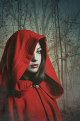 Dark red hooded woman in a misty forest
