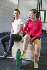 Two smiling women rests at fitness gym center