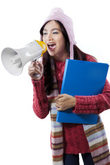 Student in winter clothes shout with megaphone