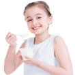 Portrait of a  little girl eating yogurt.