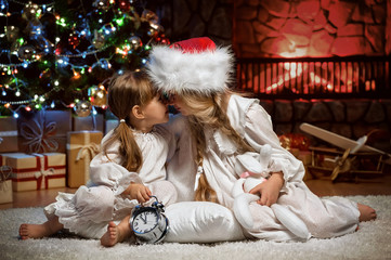 Portrait of childrens under the Christmas tree by the fireplace