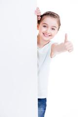 Smiling little girl holding empty white banner.