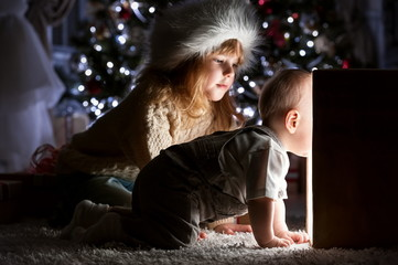 Children in Christmas night under the tree with a magical gift