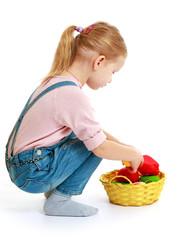 Girl considers lying in a basket of fruit.