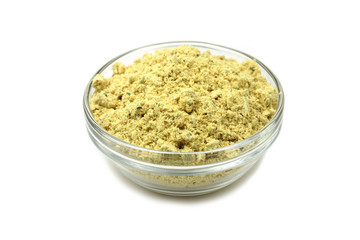 little yellow spice in a glass container on a white background