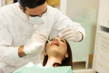 caucasian dentist is visiting an asian woman