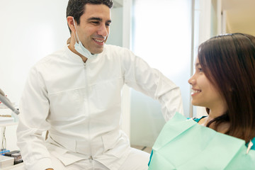 asian male dentist is speaking with his patient