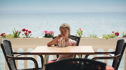Child is drinking water in the restaurant near the sea