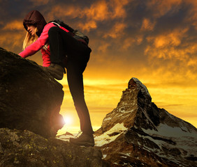 Girl on rock, in the background mount Matterhorn at sunset