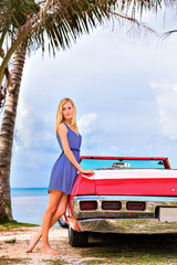 Portrait of beautiful woman standing next to the car