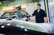 Leinwandbild Motiv Man worker washing luxury car on a car wash