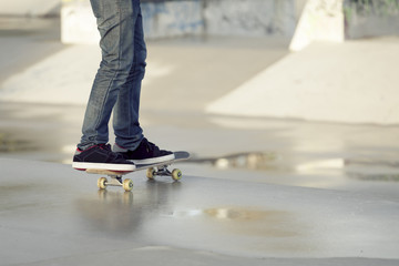 Teenager skateboarding in park in rainy day