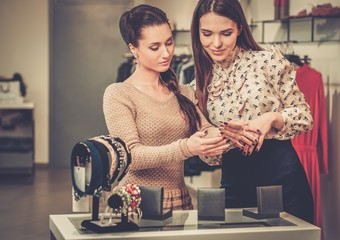 Young woman choosing jewellery with shop assistant  help