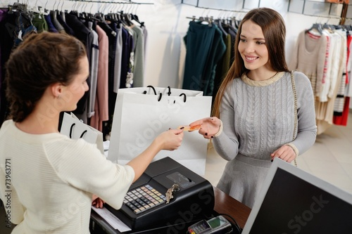Leinwanddruck Bild Happy woman customer paying with credit card in fashion showroom