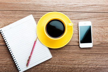 Office desk with notebook, mobile smartphone and coffee cup.