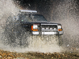 jeep passes through the water creating large spray of water