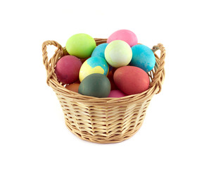 Colorful Easter eggs inside straw wicker brown basket isolated